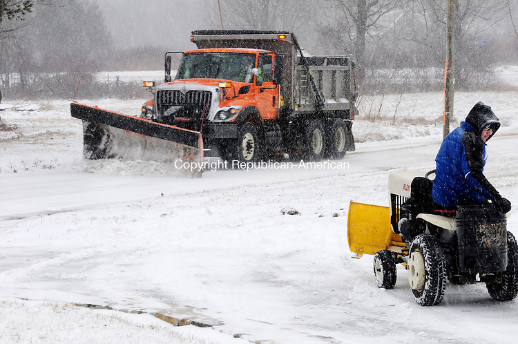 PLYMOUTH CT, 08 FEB 13-020813AJ01-   Enzo Iuliano, 16, of Terryville plows his parents' driveway Friday afternoon with a circa 1967 Bolens lawn tractor as a Town of Plymouth snowplow passes on Harwinton Ave.  Alec Johnson/ Republican-American