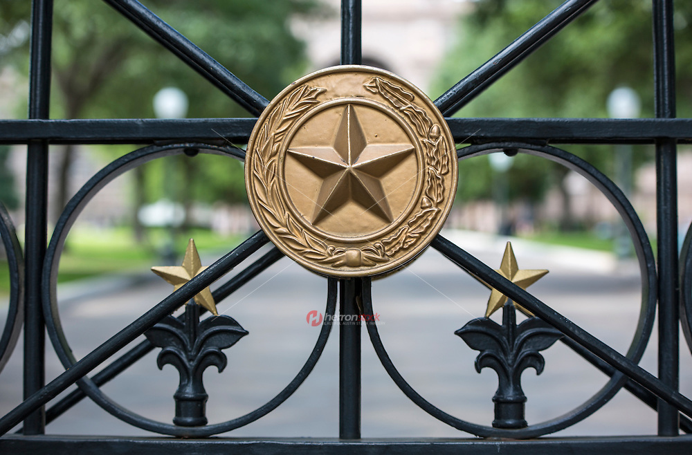 A close up of a gate at the Texas State Capitol grounds displaying the national coat of arms of the Republic of Texas, a golden lone star encircled by olive and live oak branches - Stock Image.