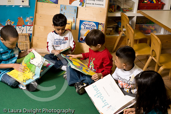 Education preschoool children ages 3-5 group of children boys and girl sitting looking at picture books separately horizontal