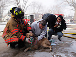 An example of a how using minimal gear in a small form-factor helps a photographer gain access:  This image was taken in the aftermath of a residential house fire.  Firemen rescued an adult dog from a burning garage and were attempting to resussitate the amimal when Price happened on the scene.  Asked to stay across the street, Price saw the scene unfolding and realized the real picture was a close-in shot of firemen with the dog.  Price pulled the external battery pack from his Olympus E-5 SLR and replaced a large zoom with a smaller wide-angle zoom.  By walking beyond the perimeter with only one small camera over his shoulder and tuned backward, he presented the impression he was neighbor, not a memeber of the media.  Firemen largely ignored Price while other media and onlookers were kept across the street.  Price was able to work largely unnoticed.