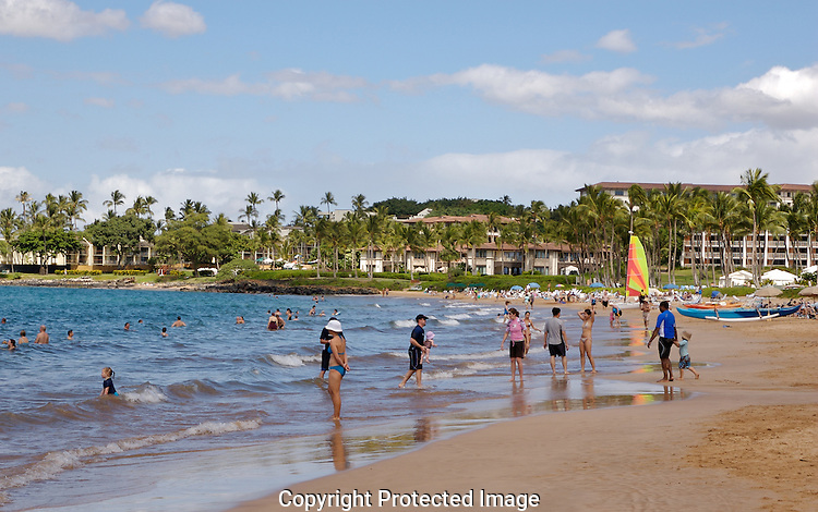 Vacationers enjoy the sun and waves off Wailea on the island of Maui.