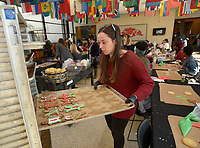 NWA Democrat-Gazette/ANDY SHUPE<br /> Allie Linstrom (right), an intern with Charwells, loads decorated cookies Wednesday, Dec. 5, 2018, onto trays during a cookie decorating event in the Connections Lounge in the Arkansas Union on the University of Arkansas campus in Fayetteville. The event, which is organized by Chartwells, is a stress-reliever for students who get to decorate two cookies, one to keep and one to donate to members of the campus community in need through the Full-Circle Food Pantry. Extra cookies will be donated to the Yvonne Richardson Community Center, LifeSource International and the Salvation Army.