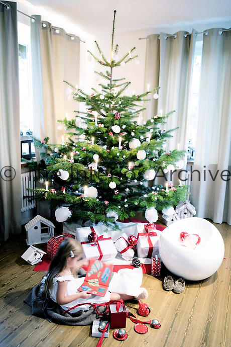 A little girl in her nightdress sitting next to the Christmas tree opening her presents on Christmas morning
