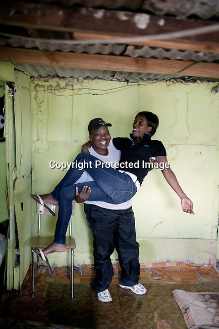 CAPE TOWN, SOUTH AFRICA - OCTOBER 19: Phato Mkhosana holds her girlfriend Brenda Tahabatha in their house on October 19, 2011 in Khayelitsha outside Cape Town, South Africa. Cape Town is a city known for tolerating gays and lesbians except in the townships where they get harassed and often attacked. Some women have been raped in so called corrective rape, where men rapes them to make them women again. They can't show their love freely on the streets in the townships so they usually have to meet in houses and this bar.  (Photo by Per-Anders Pettersson)