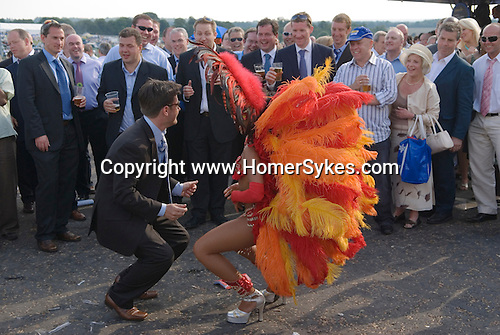 The Vodaphone Derby Day Horse Racing. Epsom Downs, Surrey, England 2007. Office party of men one dances with a dancers in feathers at the end of the days racing.