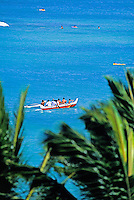 A group of tanned local paddlers navigate their Hawaiian outrigger canoe out to sea. The beautiful blue of the Pacific Ocean is framed by lush green palm fronds in foreground.