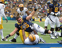 Dominic Galas of California lands on top of Vontaze Burfict of ASU after Galas lost his balance after the whistle during the game at Memorial Stadium in Berkeley, California on October 23rd, 2010.  California defeated Arizona State, 50-17.