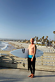 USA, California, San Diego, surfer holding his board at Ocean Beach