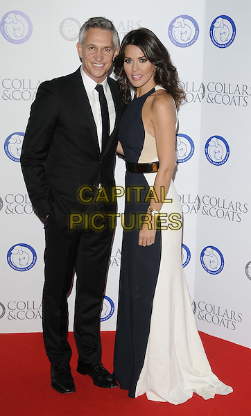 Gary Lineker & Danielle Lineker.Attending the Battersea Dogs & Cats Home 'Collars & Coats Gala Ball 2012' held at Battersea Evolution, London, England, UK, 8th November 2012..full length black suit tie white beige nude dress navy blue belt colour block married couple husband wife long maxi .CAP/CAN.©Can Nguyen/Capital Pictures.