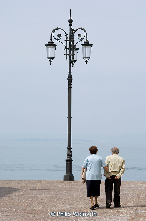 An elderly Italian couple walk by Lake Garda in northern Italy