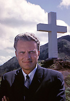 Reverend Billy Graham beneath giant cross at Kolekole Pass, Hawaii, 1963. Photo by John G. Zimmerman.