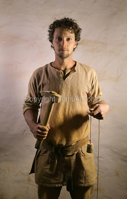 Baptiste Fabre, bricklayer on the Guedelon project since 01/04/2014, wearing medieval costume and holding a wooden hammer and plumb line, at the Chateau de Guedelon, a castle built since 1997 using only medieval materials and processes, in Treigny, Yonne, Burgundy, France. The Guedelon project was begun in 1997 by Michel Guyot, owner of the nearby Chateau de Saint-Fargeau, with architect Jacques Moulin. It is an educational and scientific project with the aim of understanding medieval building techniques and the chateau should be completed in the 2020s. Picture by Manuel Cohen