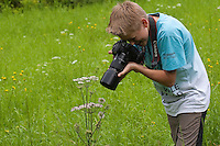 Kind, Junge fotografiert in der Natur, auf einer Wiese, Fotografieren, Naturfotografie, Child, boy photographs in nature, in a meadow, photography, nature photography