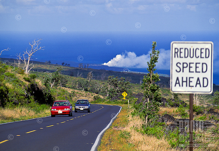Cars drive on Chain of Craters Road with lava entering the ocean in the distance. Hawaii Volcanoes National Park. Hawaii