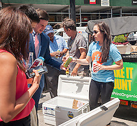 Workers give out samples of Blueprint brand organic cleanse in Flatiron Plaza in New York on Wednesday, June 22, 2016. Blueprint manufactures organic juices and body cleanses in a variety of flavors.  (© Richard B. Levine)