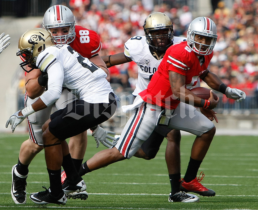 Ohio State Buckeyes tight end Reid Fragel (88) throws a block on Colorado Buffaloes defensive back Greg Henderson (20) to free up teammate Ohio State Buckeyes quarterback Braxton Miller (5) in the first quarter of their NCAA football game at the Ohio Stadium in Columbus, September 25, 2011.  (Dispatch photo by Neal C. Lauron)
