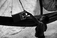A Nukak boy turns on the radio, given them by missionaries, in a refugee encampment close to San Jose del Guaviare, Colombia, 3 September 2009. The Nukak Maku people, nomadic hunter-gatherers from Amazonia, were violently driven out of the jungle by the Colombian guerilla and paramilitary squads. Now, roughly cut off their original tribal lifestyle, they stuck between worlds. They learn from the (mainly Christian) aid workers to use clothes, to listen to the radio, to beg for money. Although their digestion suffer, they love to eat sweets, cookies and other western food. They have hunted out all the animals around and now there is nothing left for them. Nukak can not return to the jungle, their world has already passed through an irreversible change.