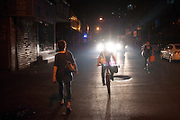 Evening landscape view of a woman on a bicycle on a street with car lights in the background near Shi Li Da Dao in the Lúshān Qū of Jiǔjiāng in Jiangxi Province.  © LAN
