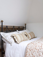 A traditional wrought-iron bed is dressed in crisp white bedding and a pink floral quilt