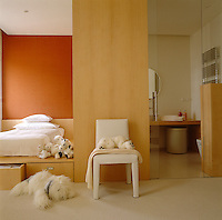 In this child's bedroom the platform bed is situated in an alcove painted a warm orange; adjacent is an en-suite bathroom