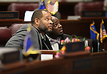 Nevada Senate Democrats Aaron Ford, left, and Kelvin Atkinson watch the big screen on the Senate floor at the Legislative Building in Carson City, Nev., on Thursday, April 9, 2015. <br /> Photo by Cathleen Allison