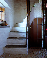 A rustic stone staircase with slate treads winds up to the traditional sleeping platform