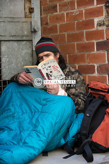 A homeless man reading a book while in his sleeping bag