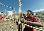 A woman fastens sticks together with strips of cloth as she builds a temporary home in a spontaneous camp for quake survivors being established in Croix-des-Bouquets, Haiti, north of the capital Port-au-Prince. Quake survivors continue to move as aftershocks continue, and reports of aid deliveries in one camp will provoke families from other camps to migrate there.