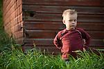 A young boy stands in a grassy field on a prairie farm in Saskatchewan, Canada.