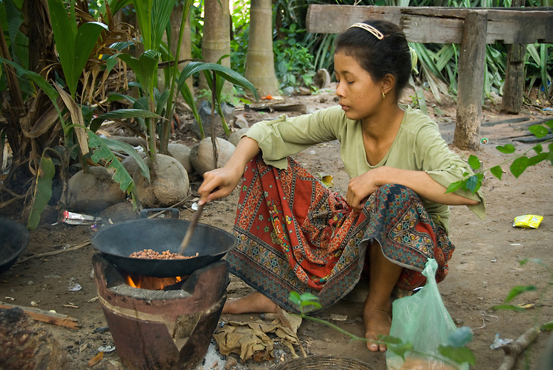 A young rural Cambodian woman roasting peanuts near Siem