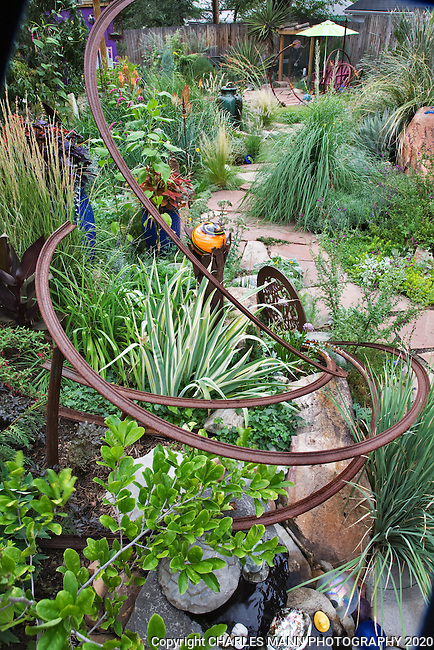 A flagstone path leading to the lower pond is filled witheye catching ornaments andvignettes in Dan Johnson's Denver garden.