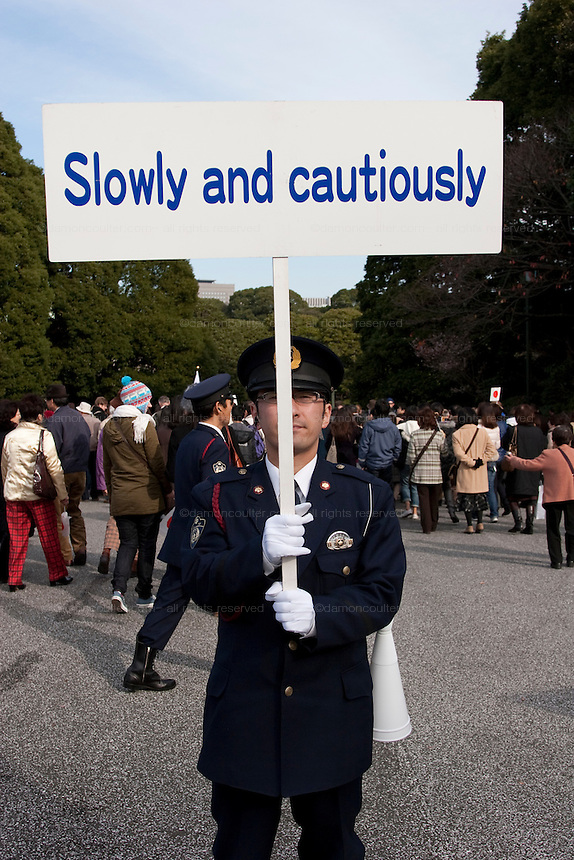 A Japanese policeman warns crowds to walk slowly and cautiously as they leave the Imperial Palace after Emperor Akihito's traditional birthday address on December 23rd 2008 in Tokyo. Japan