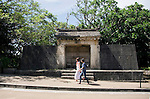Visitors walk past Sonohyan-utaki Ishimon, a stone gate that leads to a sacred grove inside the grounds of Shuri-jo Castle Park in Naha, Okinawa Prefecture, Japan, on June 24, 2012. The gate is one of a number of historical sites in Okinawa that are designated collectively as a UNESCO World Heritage Site. Photographer: Robert Gilhooly