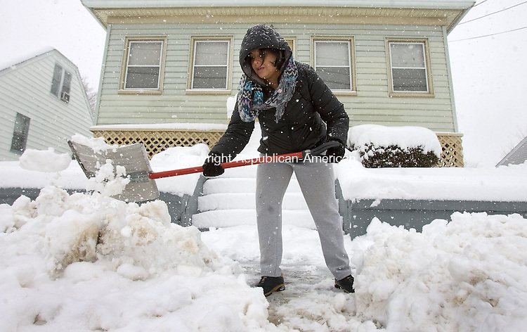 WATERBURY, CT. 08 March 2013-030813SV10-Sabine Sosiah of Waterbury deals with yet another storm while she tries to clear snow from in front of her home on Bradley Avenue in Waterbury Friday..Steven Valenti Republican-American