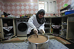 """A Palestinian woman Dalal al-Bardawil, 53, prepares """"Samaqia"""", traditional meal of Gazans, to sell it for customers, at her own kitchen in Gaza city on March 14, 2018. Samaqia consists of """"meat, onions, flour, spices, olive oil, cicla, sumach and Red tahini"""". Palestinians in Gaza strip deliver Samaqia dishes in weddings and holidays. Photo by Mahmoud Ajour"""