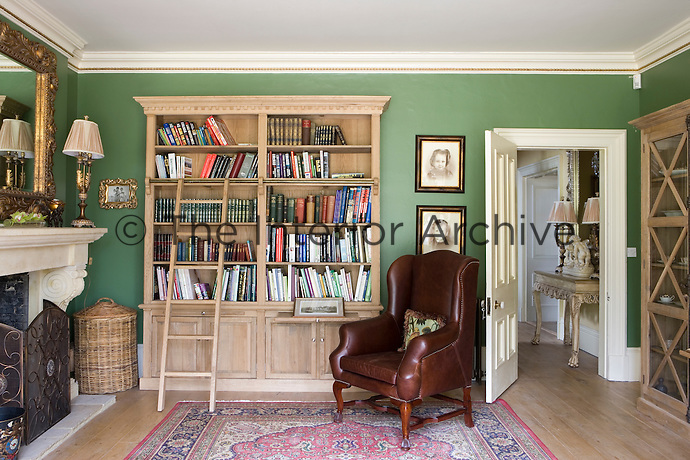 Wooden book shelf with brown leather armchair