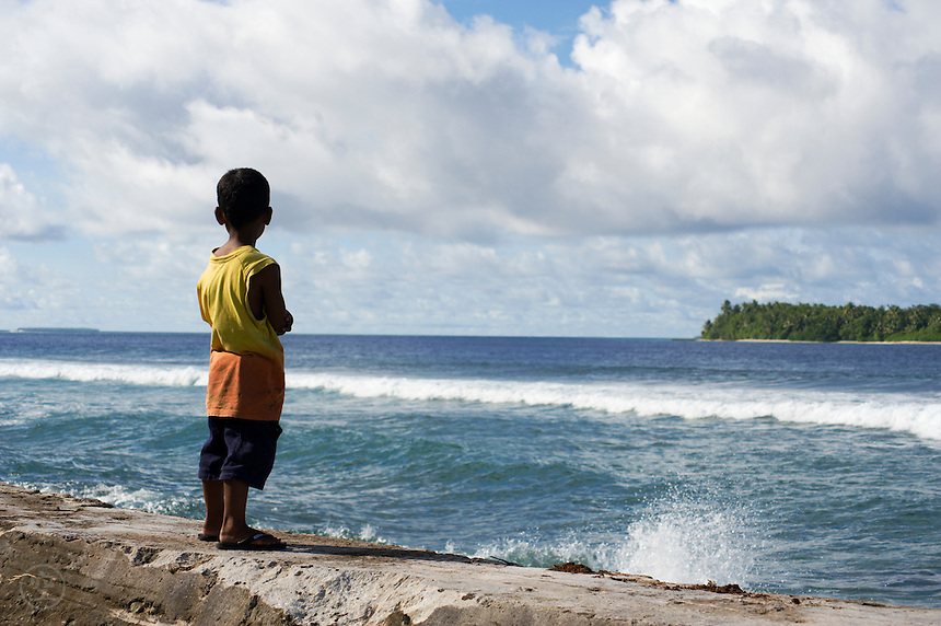 A young boy stands on a sea wall and gazes out at the ocean on Jaluit Atoll.