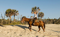 A woman rides a horse through the sand along the beach in Amelia Island, FL