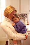 young mother standing in kitchen holding distressed toddler in her arms, parenting