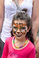 A smiling girl showing off her cat face painting.