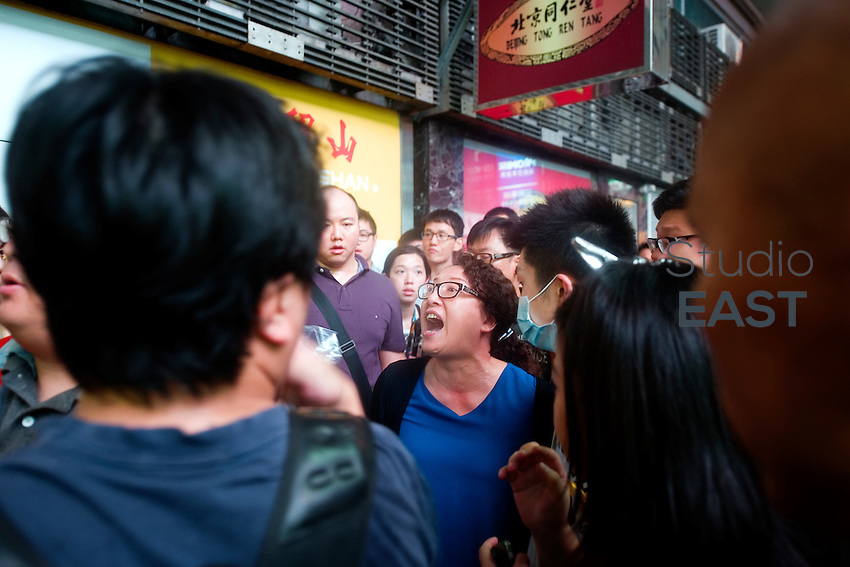 HONG KONG, HONG KONG SAR, CHINA - OCTOBER 03: An anti-Occupy protester yells at pro-democracy protesters, saying she works here and that they disturb her work, in Jardine's Bazaar, in Causeway Bay, Hong Kong, on October 3, 2014. Protesters, who also have suffered attacks from anti-Occupy protesters, have started to regroup their supplies stations to stronger positions. Also called the 'Umbrella revolution', the 'Occupy Central' civil disobedience movement began in response to China's decision to allow only Beijing-vetted candidates to stand in the city's 2017 election for the top civil position of chief executive. Protest leaders demanded the resignation of Hong Kong's Chief Executive C.Y. Leung Chun-ying, who failed to comply. (Photo by Lucas Schifres/Getty Images)