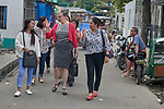 """Harriett Olson (in red sweater), the chief executive officer of United Methodist Women, walks through the Manila North Cemetery in Manila, Philippines, on January 16, 2018.  On her left is Christian """"Love"""" Gagno, the program director for the UMW-supported Kapatiran-Kaunlaran Foundation (KKFI), which carries out educational and other work in the cemetery. On her right is Melanie Betanio, a young woman from the cemetery who is doing university studies with help from a scholarship from KKFI. <br /> <br /> Olson was in the Philippines to meet with women from throughout the region."""