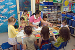 Berkeley CA  Latina teacher and students working on art projects at bilingual Spanish-English preschool