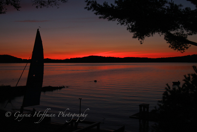Evening red sunset on lake. Sailboat, mountains, trees, silhouetted. NH