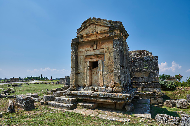 Picture of  A18 of the Tomb North Necropolis. Hierapolis archaeological site near Pamukkale in Turkey.<br /> <br /> Tomb A 18 ( 1st century AD) <br /> <br /> The building, one of the most representative and best conserved of the North Necropolis, has the shape of a small temple, built to a square plan with regular walls. The facade is framed by projecting pilasters; the roofing slabs rest on the, two frontons and the lateral cornices.- Beneath the base is a subterranean chamber partially carved into of the rock. The two chambers have sepulchral beds along the walls.