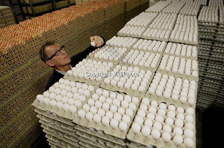 """Foto: VidiPhoto..BARNEVELD - Bij het eier-inpakstation Kwetters in Barneveld worden donderdag 150.000 witte eitjes gesorteerd en ingepakt voor de Nederlandse voedselbanken. De gratis kersteieren zijn geschonken door de Nederlandse pluimveehouders (Nederlandse Vakbond Pluimveehouders, NPV). Het grootste eier-inpakstation van Nederland, Kwetters, stelt -eveneens gratis- personeel en machines beschikbaar om de eieren in de pakken in doorzichtige doosjes van tien stuks met de tekst: """"NVP maatschappelijk betrokken"""". Maandag worden de eieren naar de voedselbankcentrale in Rotterdam gebracht. Foto: Bedrijfsleider Henk van Veldhuizen controleert de zojuist binnengekomen zending kersteieren."""