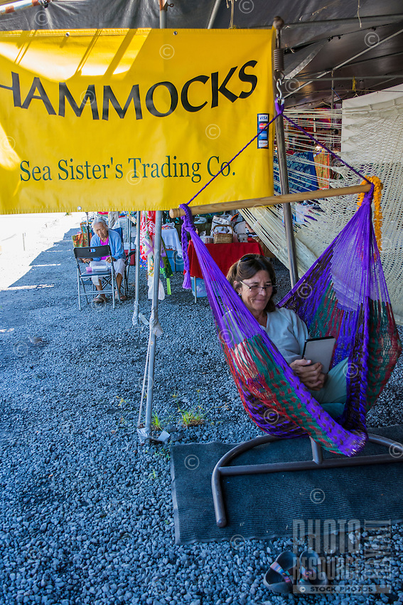 A vendor relaxes in a sitting hammock at Hilo Farmers Market, Big Island of Hawai'i.