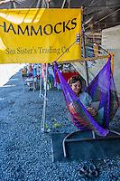 A vendor relaxes in a sitting hammock at Hilo Farmers Market, Big Island of Hawai'i.
