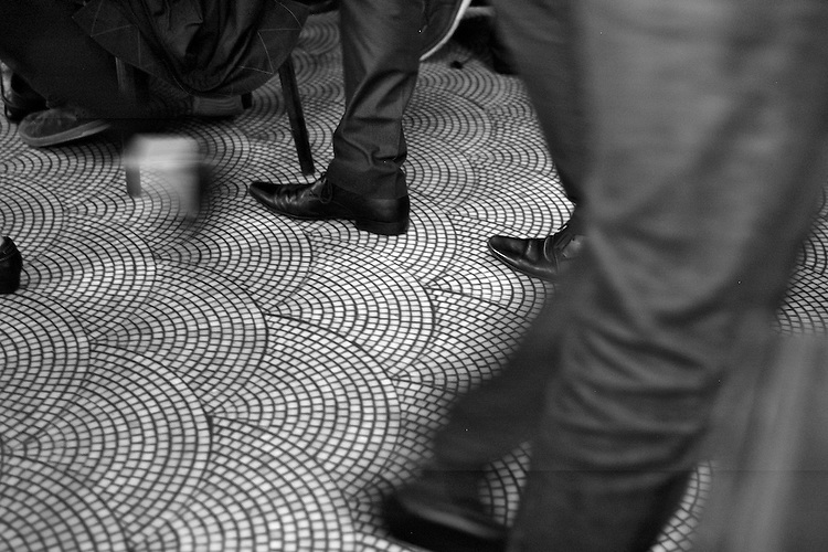 A view of the floor with a variety of formal shoes against a patterned tiled floor.  Certainly my dress code was always too casual for New York city.