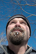 Close-up of a hiker's beard covered with ice on the side of a hiking trail in the White Mountain National Forest, New Hampshire USA.